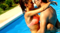 Loving couple in a swimming pool. video