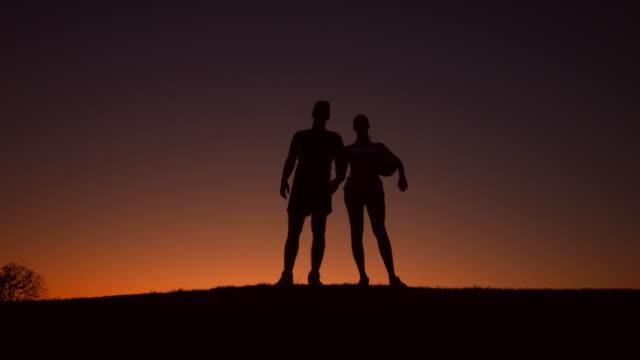 Loving couple of sportsmen walk on the evening hills. video