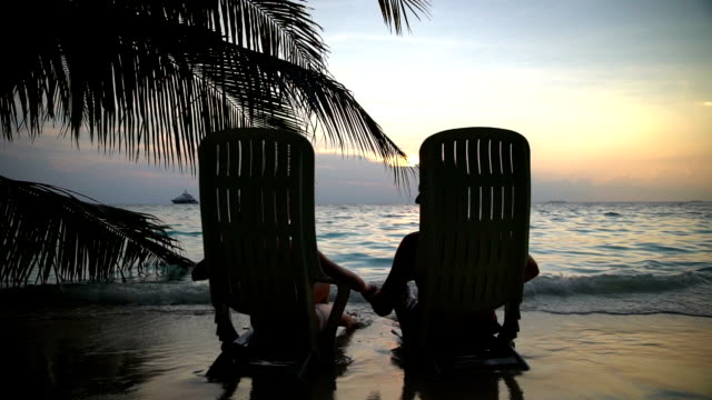 Loving couple on a tropical beach are admiring the sunset and kissing. Slow motion. video