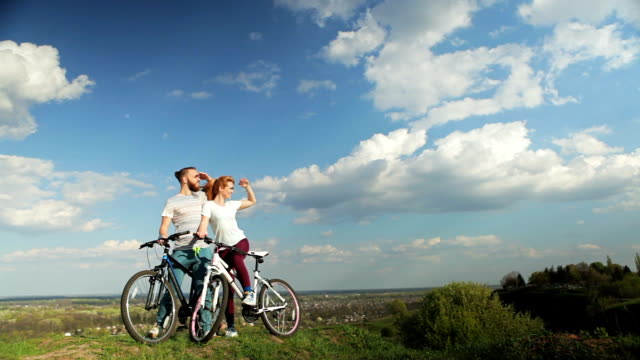 Loving couple on bicycles standing on a high hill. video