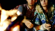 A loving couple relaxing by the fire, drinking beer video
