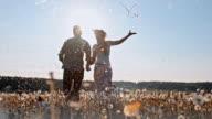 SLO MO Loving couple running among dandelion seeds video