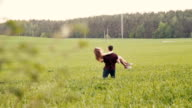 Loving couple swirl around in a field. Happy man and woman look at each other, womans hair sway in the air, slow mo video