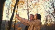 Loving couple taking selfies in autumn forest video