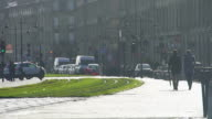 Loving couple walking near tram tracks, traffic on road, city life in slow-mo video