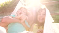 Loving mother and children laughing together in a hammock video