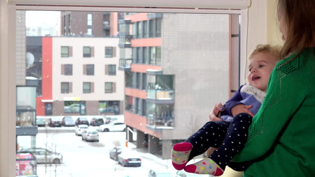 Loving mother swing naughty daughter girl on hands near window. Snow fall video
