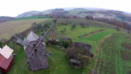 Low aerial flyover view of old wooden windmill video
