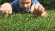 low angle crazy man cutting grass with scissors video