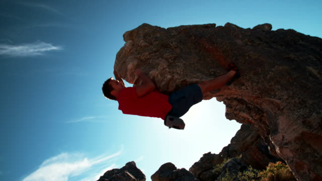 Low angle of extreme free climbing man hanging on rock video