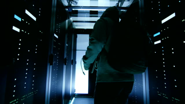 Low Angle Shot of a Masked Hacker in a Hoodie Sneaking Through Corporate Data Center with Rows of Rack Servers. video