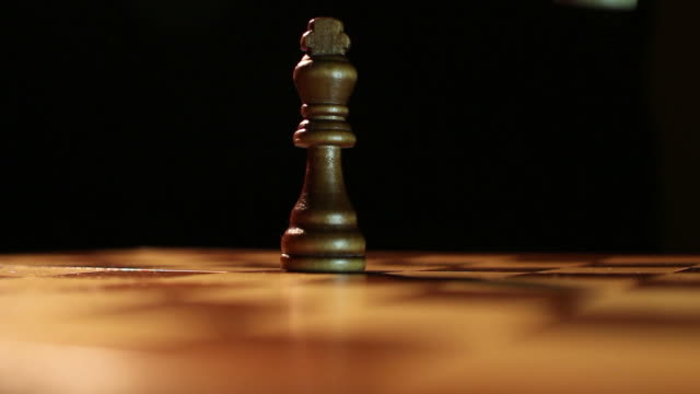 Low angle shot of the king chess pieces standing on a chess board and the white king hits and overthrows the black king video