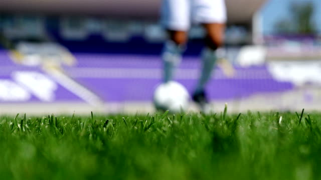 Low angle view of a footballer leading the ball on a football field video