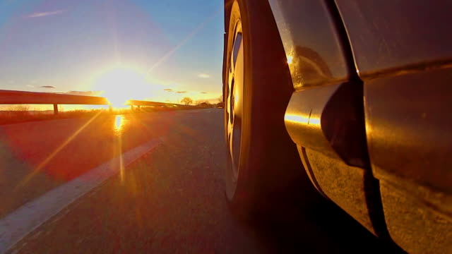low angle view of car, sunset rays shining on tire video