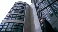 Low angle view of confident businessman standing near office building video