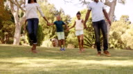 Low angle view of happy family holding hands and walking video