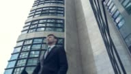 Low angle view of office building with confident businessman video