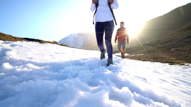 Low angle view of two hikers walking on snowy mountain trail video