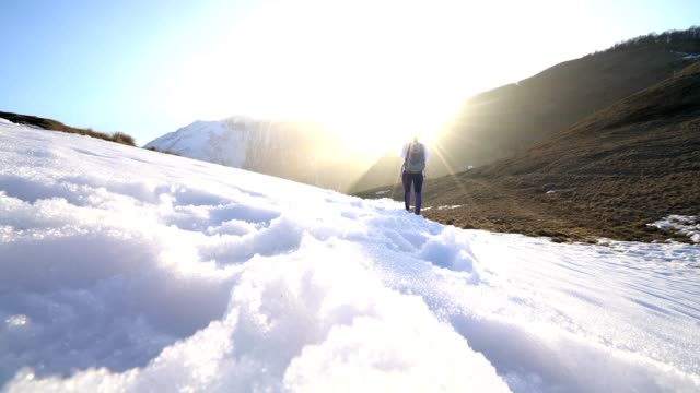 Low angle view of woman's feet walking on snowy mountain trail video