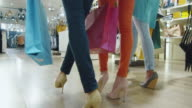 Low shot of female legs walking outwards the camera through a department store in colorful garments. video