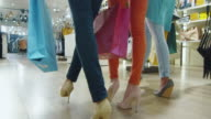 Low shot of female legs walking through a department store in colorful garments. video