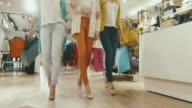 Low shot of female legs walking towards the camera through a department store in colorful garments with shopping bags. video