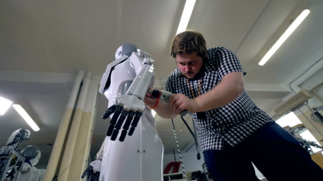 A low view on a man attaching robots plastic body. video