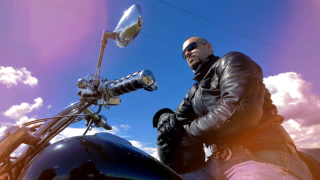 A low view on a motorcyclist wearing black sunglasses. 4K. video