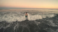 Low-altitude aerial footage of the young man walking into the water to swimming at sunset, Long Island, New York State. video