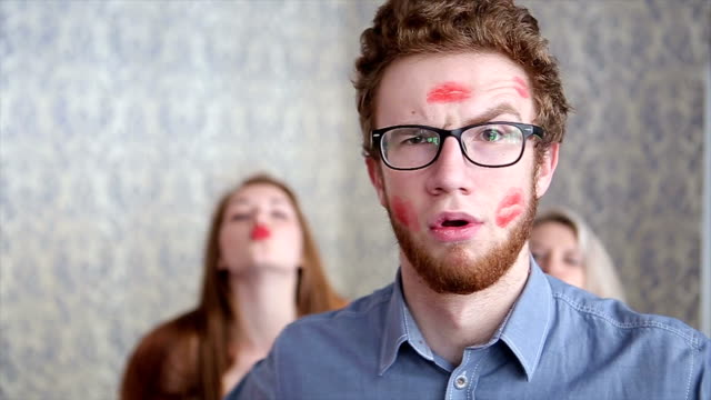 Lucky Guy Covered in Kisses by Beautiful Young Girls on Light Background video
