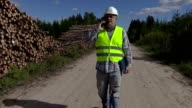 Lumberjack talking on smartphone and walking near log piles video