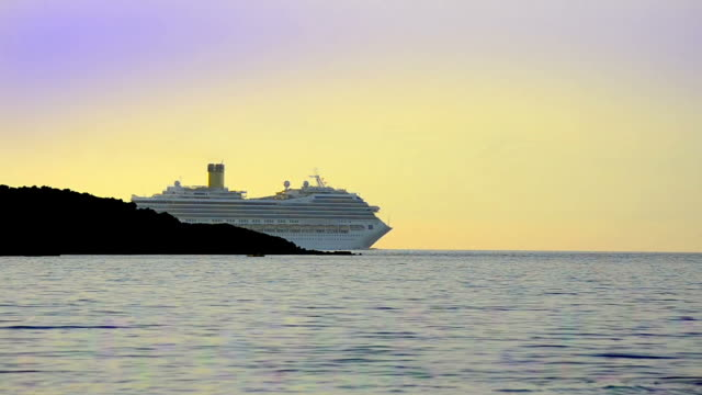 Luxury cruise ship sailing on ocean sunset horizon video