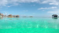 4K UNDERWATER: Luxury empty infinity swimming pool in high class hotel resort with deluxe overwater villas in the background on a beautiful sunny day in summer video