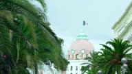 Luxury five-star hotel, French flag waving on roof, beautiful city architecture video
