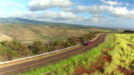 AERIAL: Luxury red convertible car driving along beautiful countryside in Hawaii video
