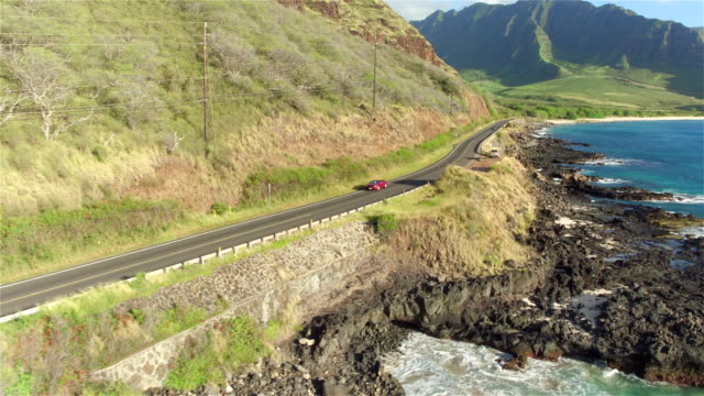 AERIAL: Luxury red convertible driving along coastal road above rocky shore video