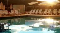 Luxury resort evening time. Pool worker folding sun umbrellas video