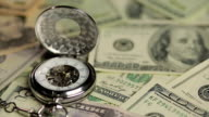 Luxury silver pocket watch on pile of US one hundred-dollar bills, time is money video