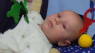Lying baby plays with hanging toys video