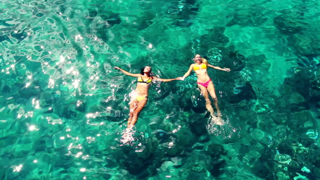 lying on a water surface in crystal clear ocean. Aerial Perspective. Summer Fun Lifestyle. video