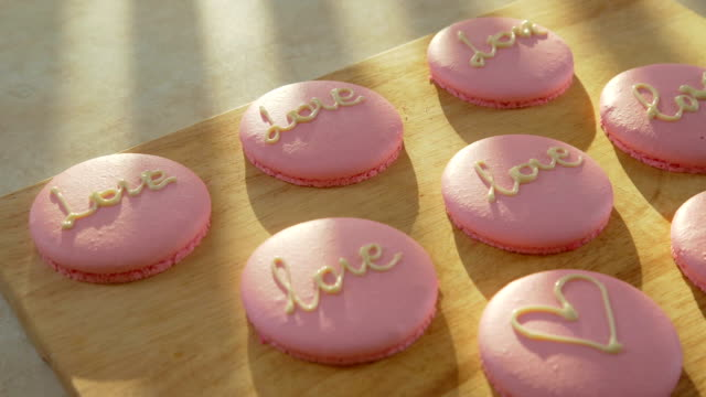 Macaroon decorated with hearts and the words 'love' for 14 February video