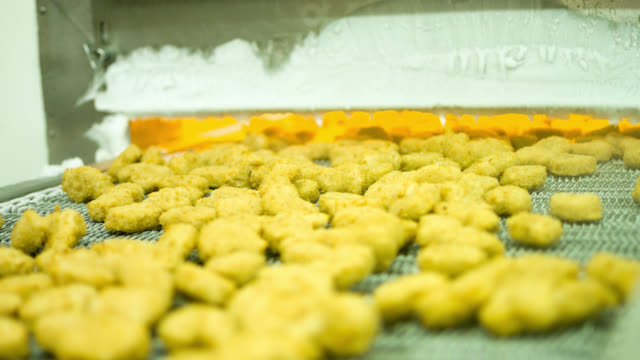 Machine baking nuggets at a chicken factory video