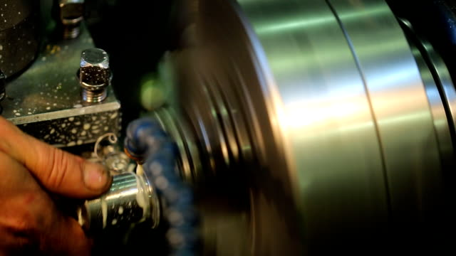 A machine operator removes a brilliant a rotating part with a milling machine with coolant video