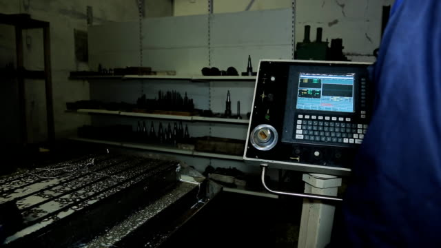 Machine operator with CNC controls it via control panel video