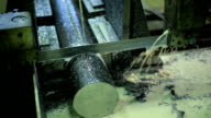 Machine with metal band saw. Cutting thick bar iron in metalworking. slow sawing thick piece of pure metal using an oil-based lubricant, and emulsions video
