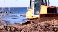 A machinery getting some soil from the lakeside video