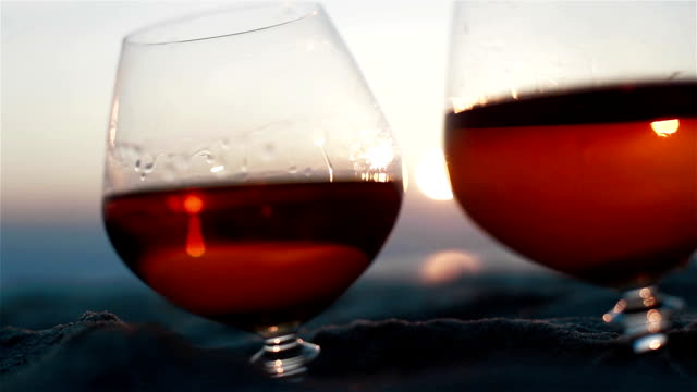 Macro extra close up of two glasses of brandy on the sand over incredible beach sunset background view video