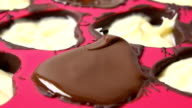 Macro FullHD video of making heart shaped chocolates in red silicone form video