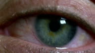 Macro shot of a woman's green eye looking tired and bloodshot video