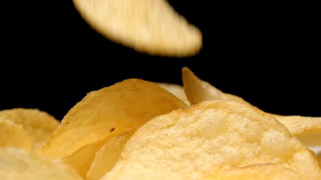 SLOW MOTION: Macro shot of falling of potato chip on a heap video